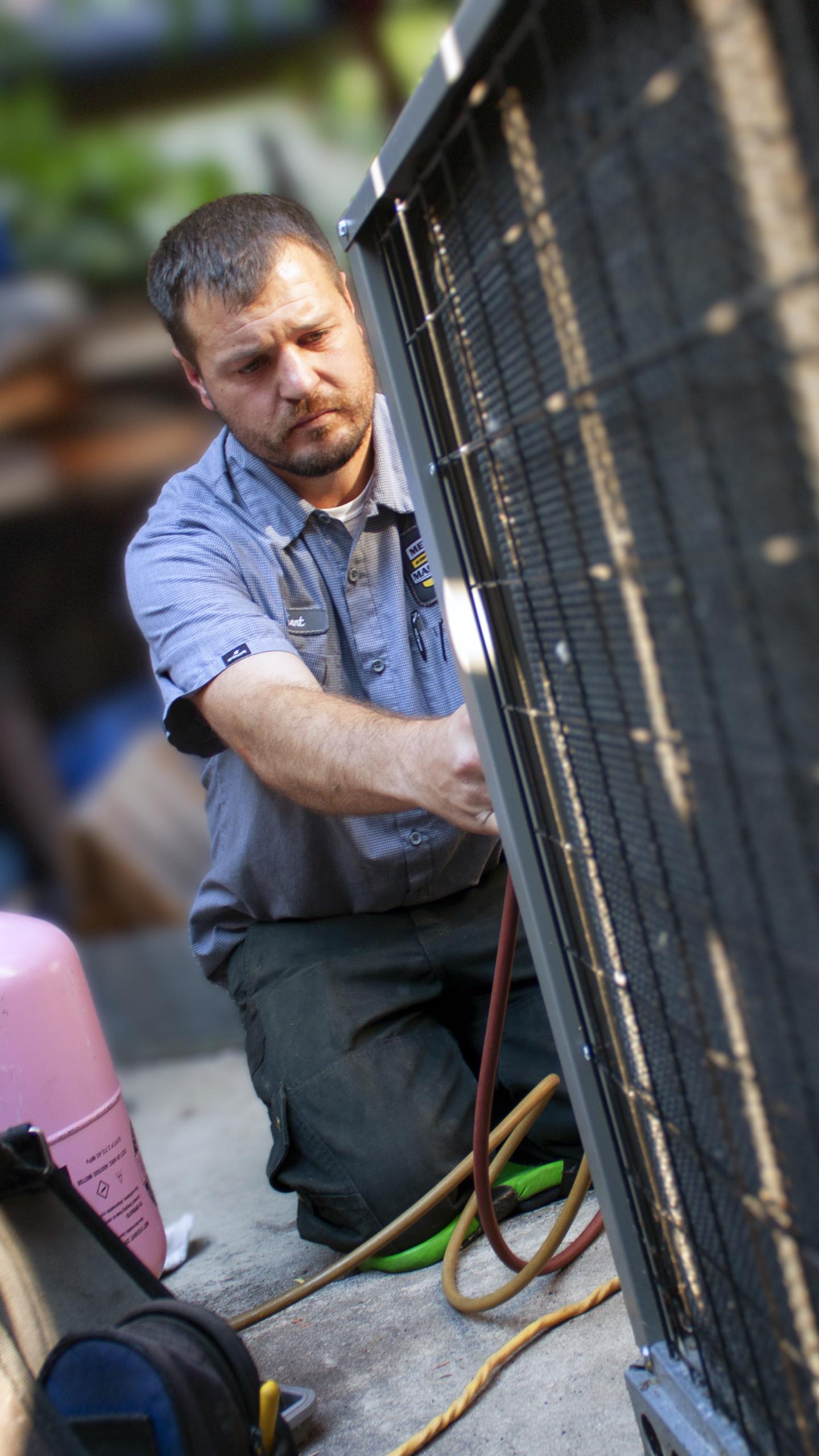 Service tech working on HVAC equipment