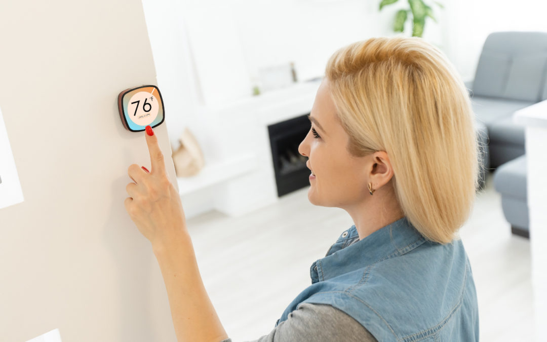 Photo of woman adjusting a thermostat